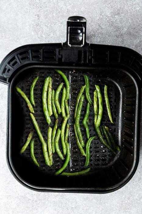 Top view of air fryer green beans in an air fryer basket