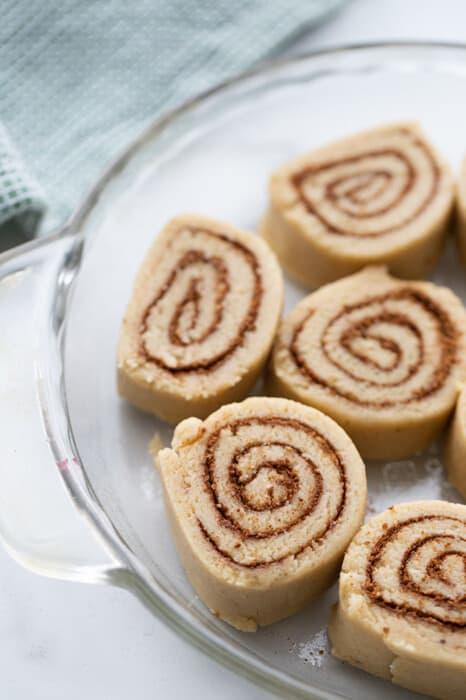 Raw cinnamon rolls in a glass pie dish