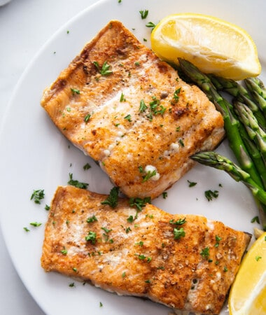 Side view of two air fried salmon filets on a white plate with asparagus and a napkin