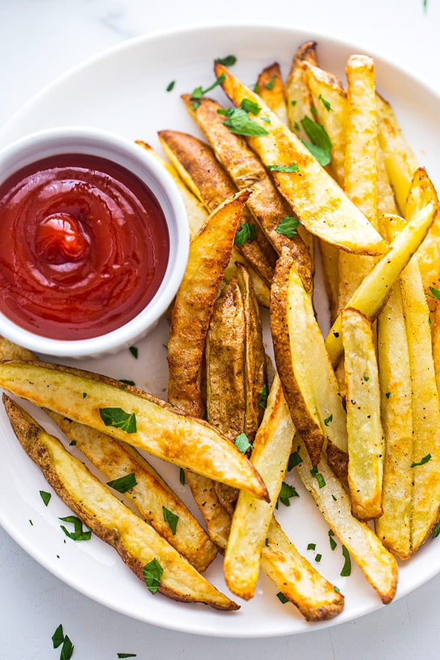 Close-up view of a white plate of crispy french fries with ketchup
