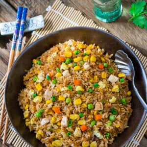 Egg fried rice in a black bowl with a spoon beside a pair of chopsticks and a glass of water