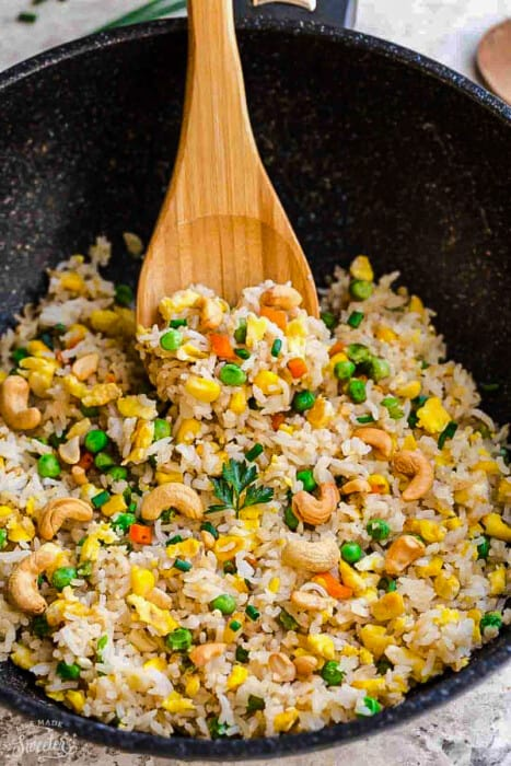 A wok full of fried rice with a wooden serving spoon scooping some out