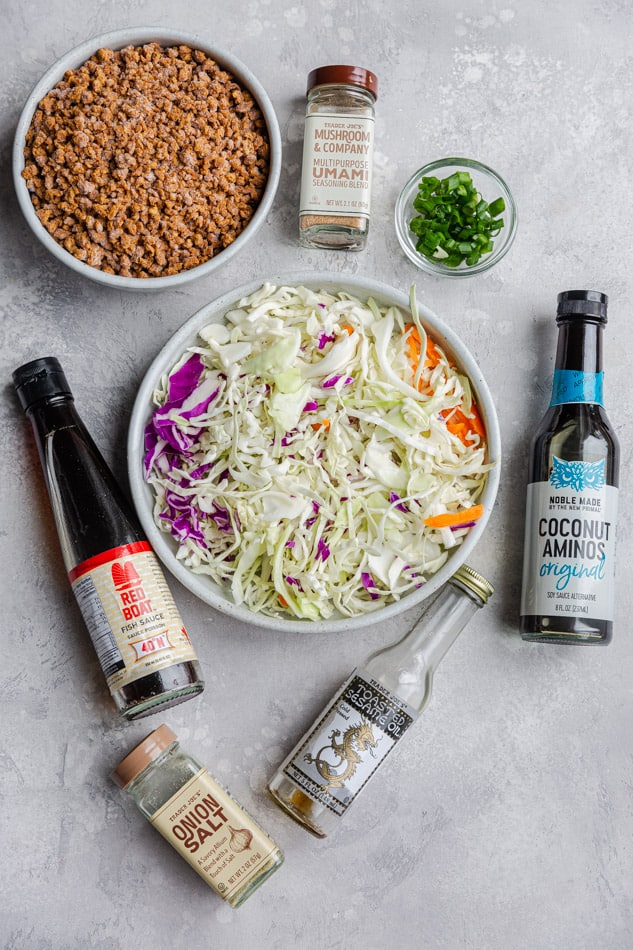 Overhead view of a bowl of shredded cabbage surrounded with bottles of ingredients for sauce