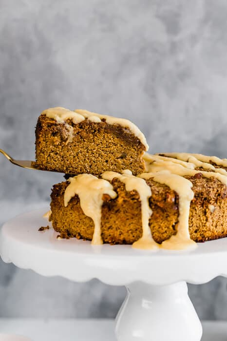 Side view of a slice of healthy pumpkin cake with on a white cake stand