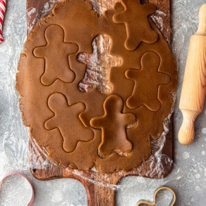 Top view of gluten free gingerbread men dough on a wooden cutting board with a rolling pin