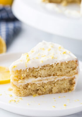 Portrait side shot of a slice of gluten free lemon cake on a white plate