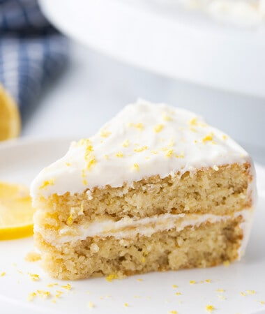 Portrait side shot of a slice of gluten free lemon cake on a white plate