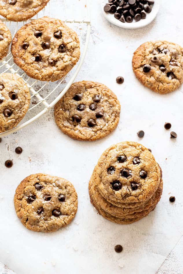 Top view of 10 gluten free chocolate chip cookies scattered on a white background with a round cookie cooling rack
