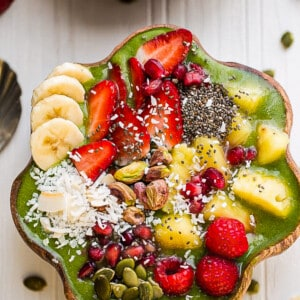 Close up top view of green smoothie recipe in a wooden bowl with fresh fruit on a white background