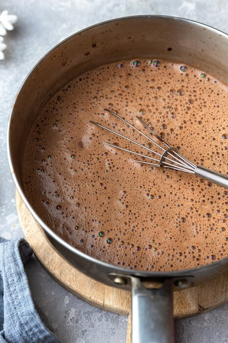 Side view of keto hot cocao mix in a pot with a whisk