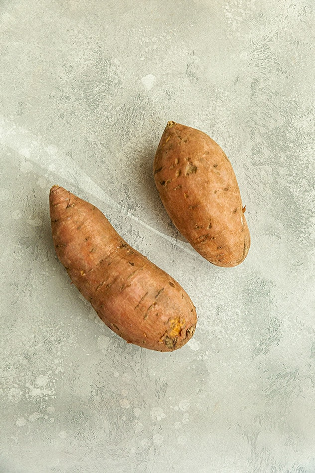 Top view of two raw sweet potatoes on a grey background