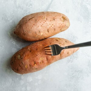 Fork piercing uncooked sweet potatoes