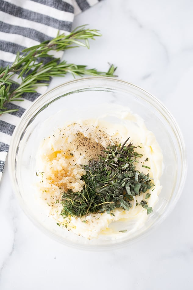 Top view of garlic herb butter in a clear bowl