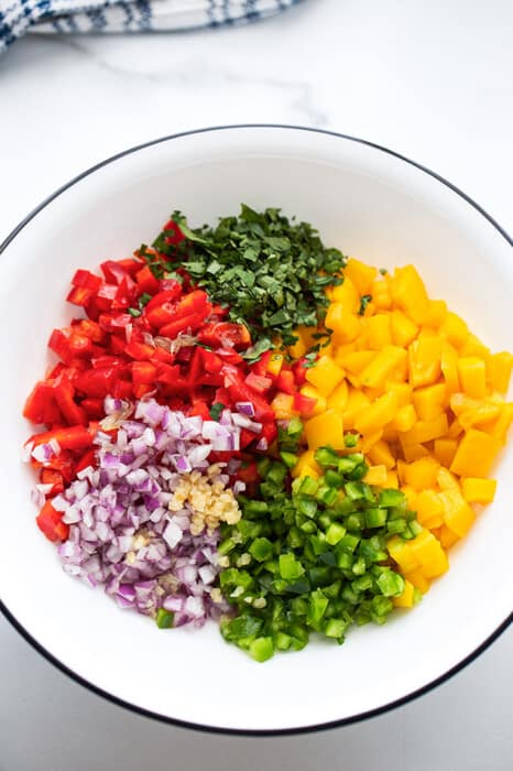 A bowl with ingredients to make mango salsa: diced mango, cilantro, jalapeno, bell peppers, garlic and red onions