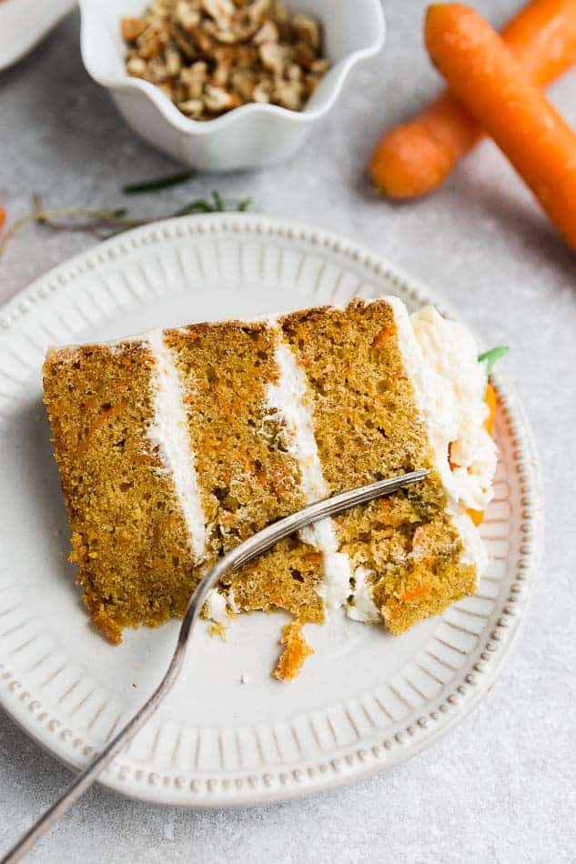 A slice of 3-layer Gluten Free Carrot Cake on a white plate with a fork