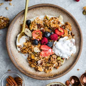 Top view of paleo granola in a white bowl with a gold spoon and coconut yogurt