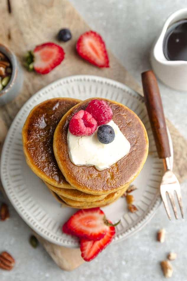 Overhead image of paleo pancakes on white plate and grey surface with wooden fork and fresh berries.