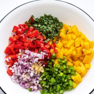 A bowl with ingredients to make peach salsa: diced peaches, cilantro, jalapeño, bell peppers, garlic and red onions