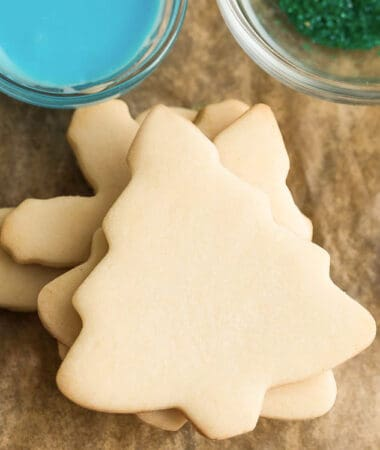 Top view of a stack of unfrosted Christmas tree sugar cookies on a wooden board