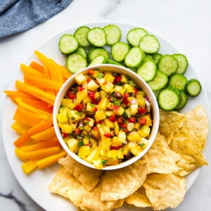 Top view of a bowl of fresh pineapple salsa served with sliced cucumbers, bell peppers and chips