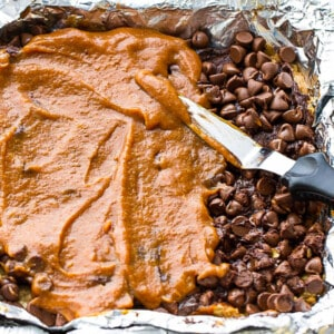 Overhead view of pumpkin being spread over chocolate chips in a foil-lined pan