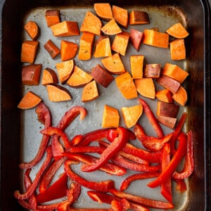 Top view of sweet potatoes and bell peppers on a baking pan