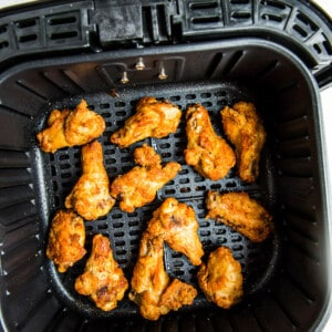 Close-up view of crispy chicken wings in an air fryer basket
