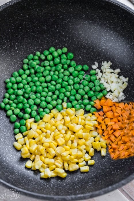 Peas, chopped carrots, corn and diced onions in a large skillet