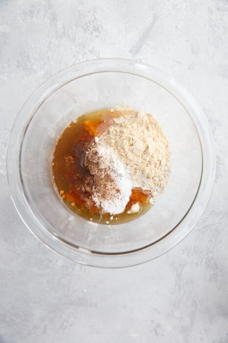 Maple Syrup, Cinnamon, Protein Powder and the Rest of the Baked Oats Ingredients in a Bowl