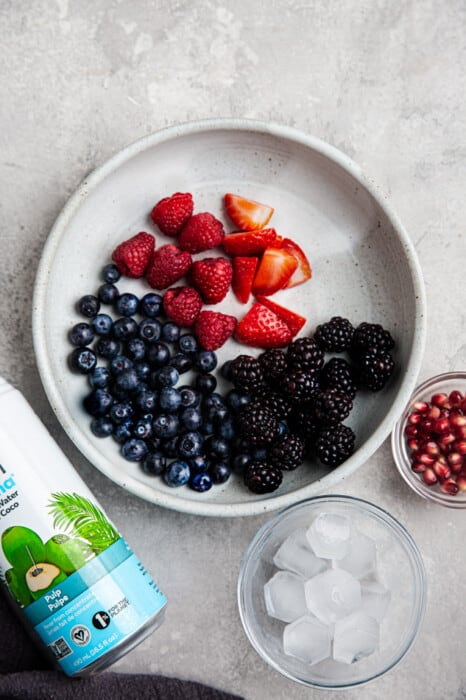 A bowl of raspberries, blueberries, blackberries and strawberries in a white bowl for nature's cereal
