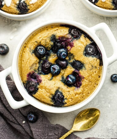 TikTok Blueberry Baked Oats in a white ramekin with a gold spoon