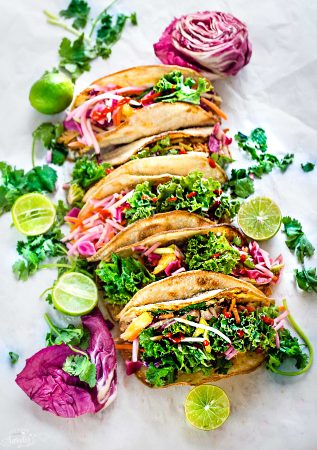 These Asian Tilapia and Kale Slaw Tacos make the perfect light and healthy weeknight meal. Best of all, easy to customize with toasted tortillas topped with flaky white fish fillets (you can use cod, tilapio or sole), a delicious kale slaw with purple cabbage, carrots, daikon and sweet pineapples. Delicious for Taco Tuesday or Cinco de Mayo!