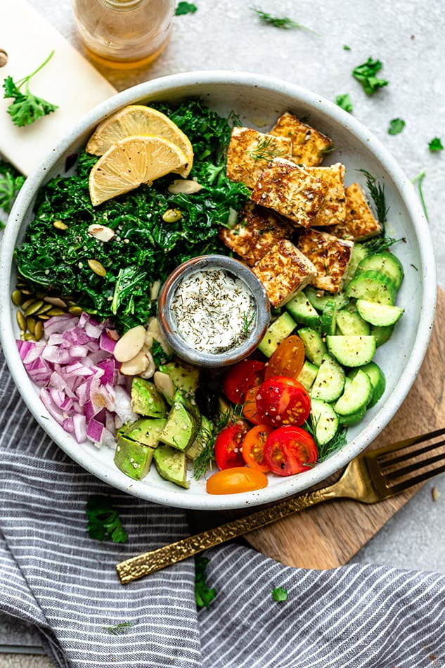 Top view of crisp tofu in a white bowl with kale, tomatoes and avocado