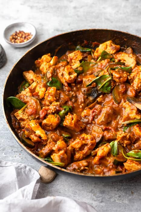 Side view of vegetable curry in dark grey pan with tofu.