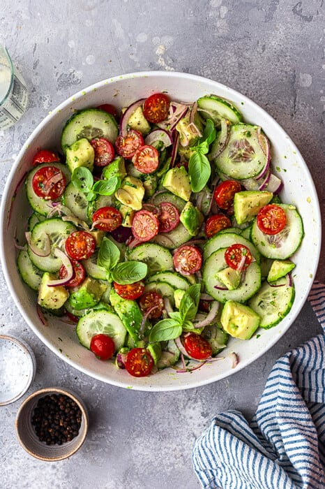 Top view of tossed cucumber tomato salad in a white bowl