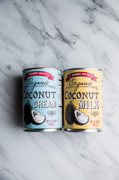 Top view of two cans of coconut cream and coconut milk from Trader Joe's on a white background