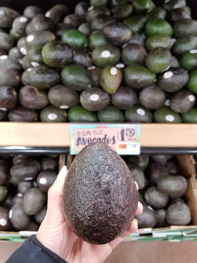 A hand holding an Avocado in front of avocados in a bin at the grocery store