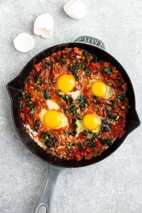 Top view of uncooked shakshuka in a grey cast-iron skillet on a grey background