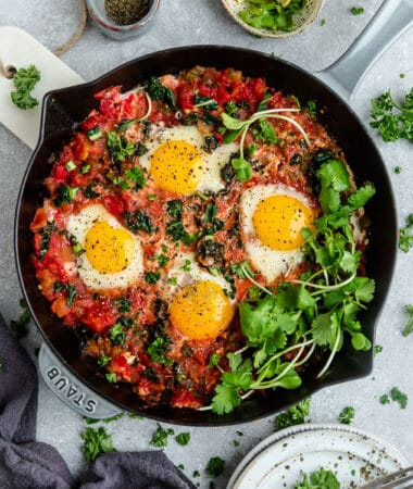 Top view of healthy shakshuka in a grey cast-iron skillet with micro-greens on a grey background