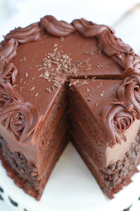 Cut out slice of simple Triple Chocolate Layer Cake with milk chocolate frosting and chocolate chips on a cake plate.
