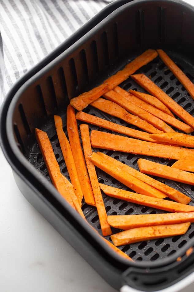 Raw sweet potato fries in the air fryer basket