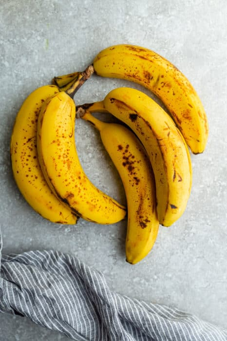 Top view of 5 spotty bananas on a grey background
