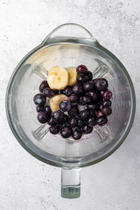 Top shot of frozen blueberries, coconut cream and milk in a blender