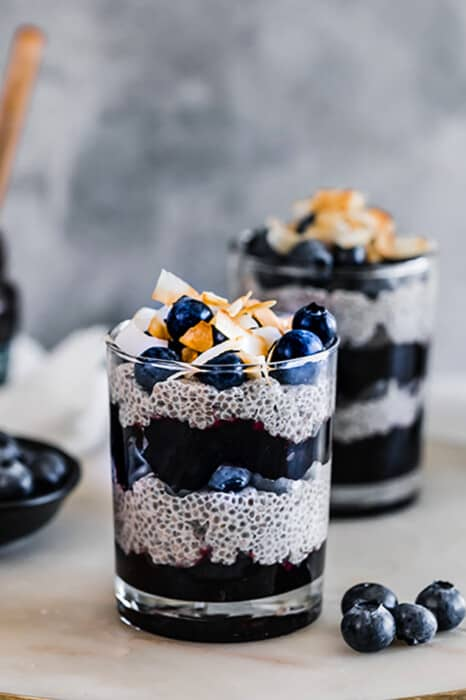 Side view of two paleo chia pudding in a cup layered with blueberries and blueberry jam with coconut chips