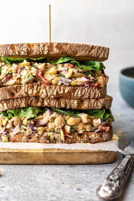 Close-up of easy chickpea salad sandwich stacked on a wooden cutting board
