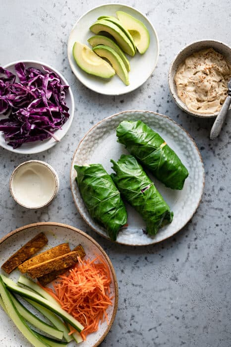 Top view of three rolled vegan collard wraps on a white plate with fresh vegetables on the side on a grey background