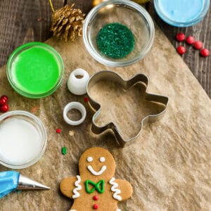Top view of decorated vegan sugar cookies on a parchment paper on a wooden background with cookie cutters