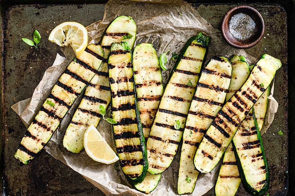 Top view of grilled zucchini arranged on parchment paper on baking sheet.