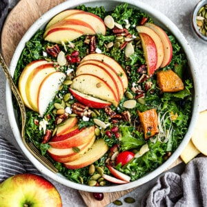 Top view of harvest salad with kale in a white bowl with sliced apples and pumpkin