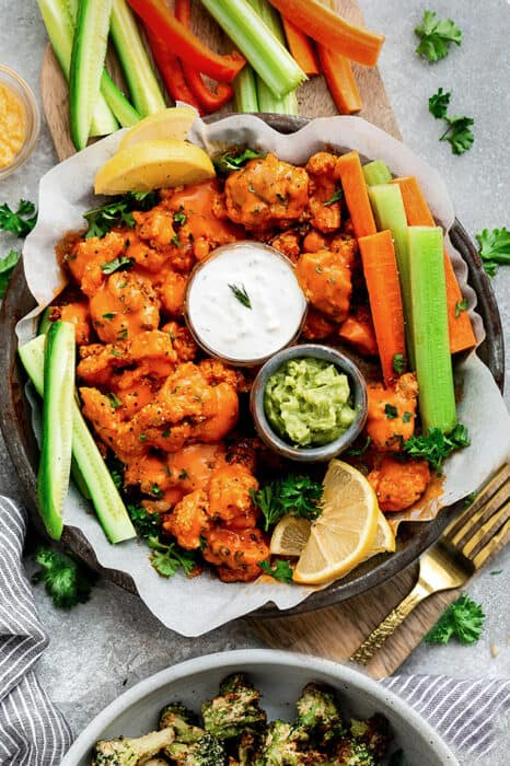 Top view of cauliflower wings in a grey plate with celery and carrots